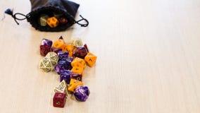 Los dados coloridos del roleplaying dispersaron en una tabla con una bolsa de lino Fotografía de archivo libre de regalías
