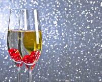 Los dados rojos que caen en las flautas de champán en el tinte de plata encienden el fondo del bokeh Foto de archivo