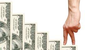 Los dedos van encima de los dólares de las escaleras Imagen de archivo