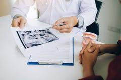 Los dentistas están discutiendo problemas dentales en la imagen de la radiografía del informe para los pacientes fotografía de archivo libre de regalías