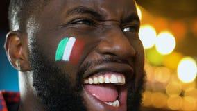 Los deportes afroamericanos avivan la victoria preferida del equipo que disfruta, bandera italiana en mejilla metrajes