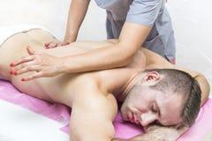 Los deportes dan masajes en la sala de masaje fotos de archivo