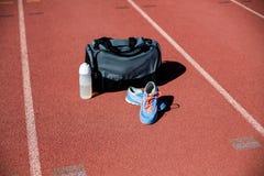Los deportes empaquetan, zapatos y una botella de agua guardada en una pista corriente Imágenes de archivo libres de regalías