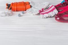 Los deportes femeninos fijaron en un fondo de madera blanco con una cuerda para saltar Fotos de archivo