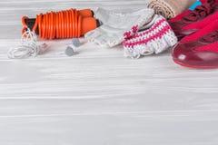 Los deportes femeninos fijaron en un fondo de madera blanco con una cuerda para saltar Fotos de archivo libres de regalías