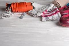 Los deportes femeninos fijaron en un fondo de madera blanco con una cuerda para saltar Foto de archivo libre de regalías