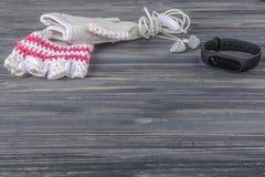 Los deportes femeninos fijaron en un fondo de madera gris con una pulsera de la aptitud Foto de archivo libre de regalías
