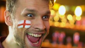 Los deportes ingleses avivan extremadamente feliz sobre la victoria preferida del equipo, bandera en mejilla almacen de video