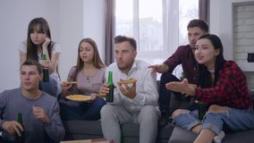 Los deportes van de fiesta, grupo de aficionados deportivos emocionados jovenes que mira el partido en la televisión mientras que metrajes
