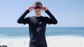 Los deportistas confiados jovenes ponen sus gafas de sol que se colocan en la playa con las ondas detrás D?a asoleado C?mara lent almacen de video