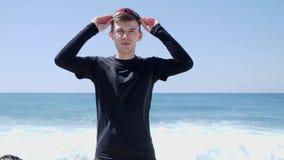 Los deportistas confiados jovenes sacan sus gafas de sol que se colocan en la playa con las ondas detr?s D?a asoleado C?mara lent almacen de video