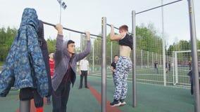 Los deportistas jovenes muestran trucos acrobáticos difíciles en barra metrajes