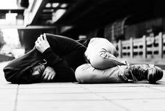 Los desamparados del hombre joven duermen en la calle Foto de archivo