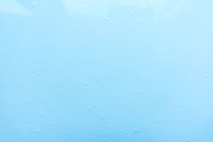 Los descensos, agua salpican en fondo azul Fondo simple lindo, contexto Visión superior Primer Foto común Imagenes de archivo