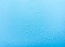 Los descensos, agua salpican en fondo azul Fondo simple lindo, contexto Visión superior Primer Foto común Fotos de archivo libres de regalías