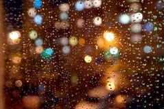 Los descensos de la noche llueven en ventana Imagen de archivo