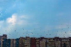Los descensos del agua fluyen abajo sobre el vidrio en la lluvia Imagen de archivo