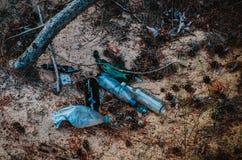 Los desperdicios se fueron por los turistas en el bosque después de una comida campestre Botellas de cristal y plásticas abandona imagenes de archivo