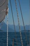 Los detalles de un velero, de una vela blanca, de cuerdas de salvamento y de hojas antes del fondo borroso del mar y de la montañ Imagen de archivo libre de regalías