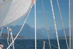 Los detalles de un velero, de una vela blanca, de cuerdas de salvamento y de hojas antes del fondo borroso del mar y de la montañ Imágenes de archivo libres de regalías