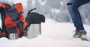 Los detalles del primer en el medio del turista del invierno consiguen una cierta bebida caliente de su termo en una taza del hie almacen de metraje de vídeo