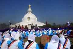 Los devotos budistas en grupo ofrecen rezos religiosos delante de la pagoda de la paz de mundo Imagenes de archivo