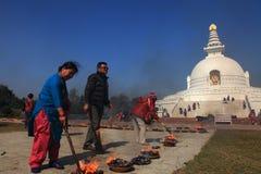 Los devotos budistas hacen rituales religiosos delante de la pagoda de la paz de mundo Foto de archivo