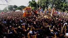 Los devotos católicos pululan durante la procesión del Nazarene negro almacen de video