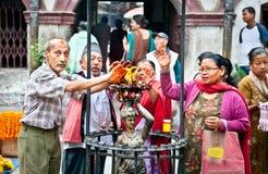 Los devotos de Hindus y de los budistas son purificación al lado de fuego en enranc Imagen de archivo libre de regalías