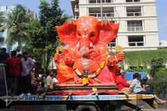Los devotos llevan el ídolo grande de Ganesha que viaja en el camino fotografía de archivo libre de regalías