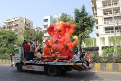 Los devotos llevan el ídolo grande de Ganesha que viaja en el camino fotografía de archivo