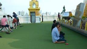 Los devotos tailandeses ruegan y caminan alrededor de stupa de oro en la cruz del soporte de oro metrajes
