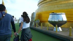Los devotos tailandeses ruegan y caminan en el templo budista del oro almacen de video