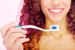 Los dientes cepillan y la sonrisa de la muchacha detrás Imagenes de archivo