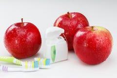 Los dientes dentales floss, cepillo de dientes y manzana roja Imágenes de archivo libres de regalías