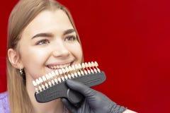 Los dientes que blanquean al dentista del procedimiento seleccionan la sombra inicial de los dientes de la muchacha imagenes de archivo
