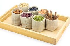 Los diferentes tipos de habas y de canela en sacos empaquetan en la bandeja de madera Foto de archivo libre de regalías