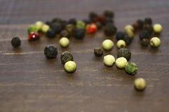 Los diferentes tipos de pimienta se dispersan en la tabla Foto de archivo
