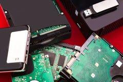 Los discos duros mienten encima de uno a en un fondo rojo Fotos de archivo libres de regalías