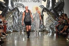 Los diseñadores David Blond y Phillipe Blond aparecen en la pista en el desfile de moda de Blonds Imagen de archivo