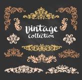 Los diseños caligráficos del oro ornamental del vintage fijaron en la pizarra Imagenes de archivo