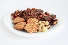 Los diversos dulces y nueces están mintiendo en la placa blanca Fotografía de archivo libre de regalías