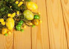 Los diversos huevos de Pascua, caramelo, flores, hierbas en fondo encienden w foto de archivo libre de regalías