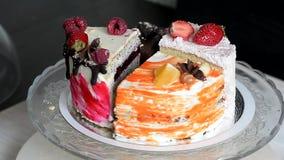 Los diversos pedazos de la torta giran suavemente en la base Hay chocolate, zanahoria, yogur y bayas metrajes