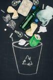 los diversos tipos de basura que caen en bote de basura exhausto con reciclan la muestra en la pizarra Imagenes de archivo