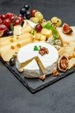 Los diversos tipos de queso en la porción de piedra suben Imagen de archivo
