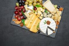 Los diversos tipos de queso en la porción de piedra suben Foto de archivo