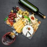 Los diversos tipos de queso y de vino en la porción de piedra suben Fotografía de archivo libre de regalías