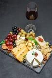 Los diversos tipos de queso y de vino en la porción de piedra suben Imágenes de archivo libres de regalías
