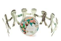 Los dólares de recortes de la gente bailan alrededor del globo Imagen de archivo libre de regalías